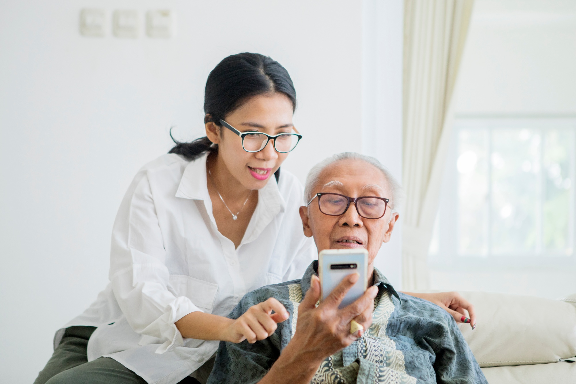 daughter helping father use smartphone