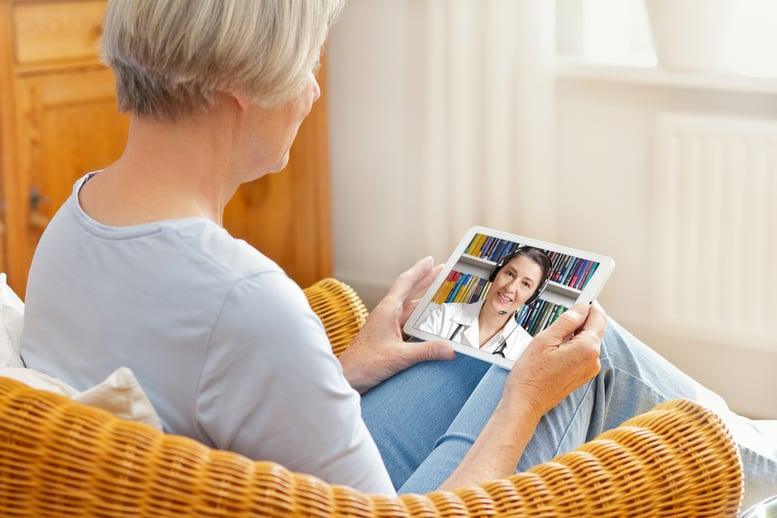 older woman using telehealth technology