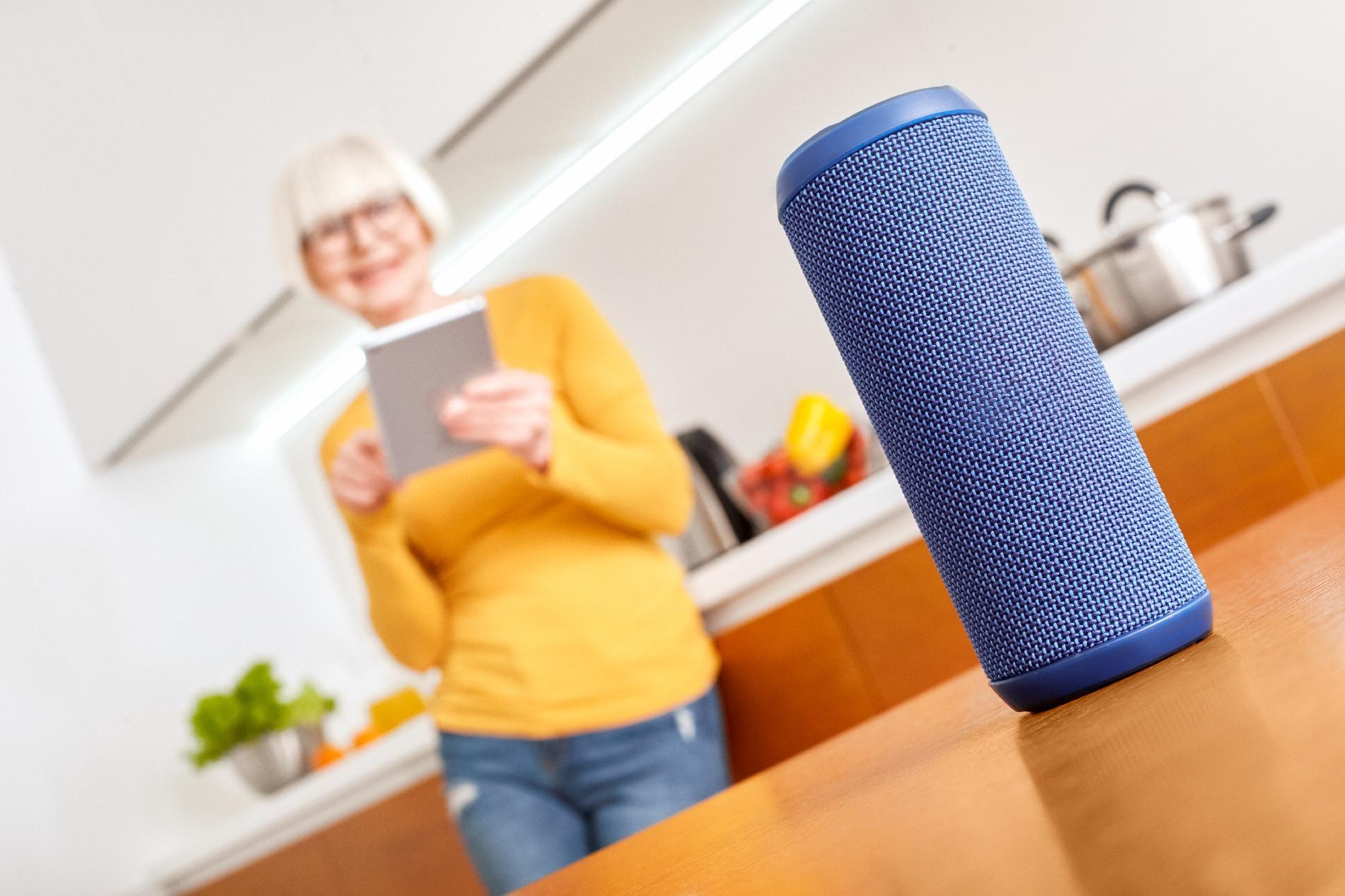 senior woman using smart speaker at home