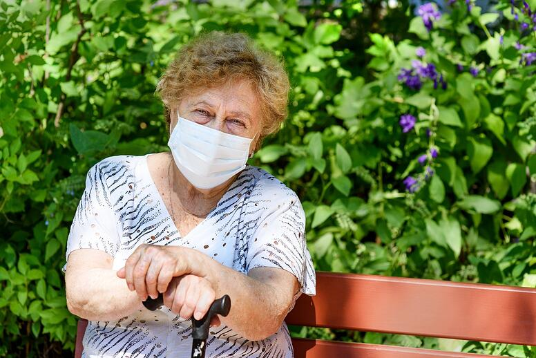 older adult woman at park with mask