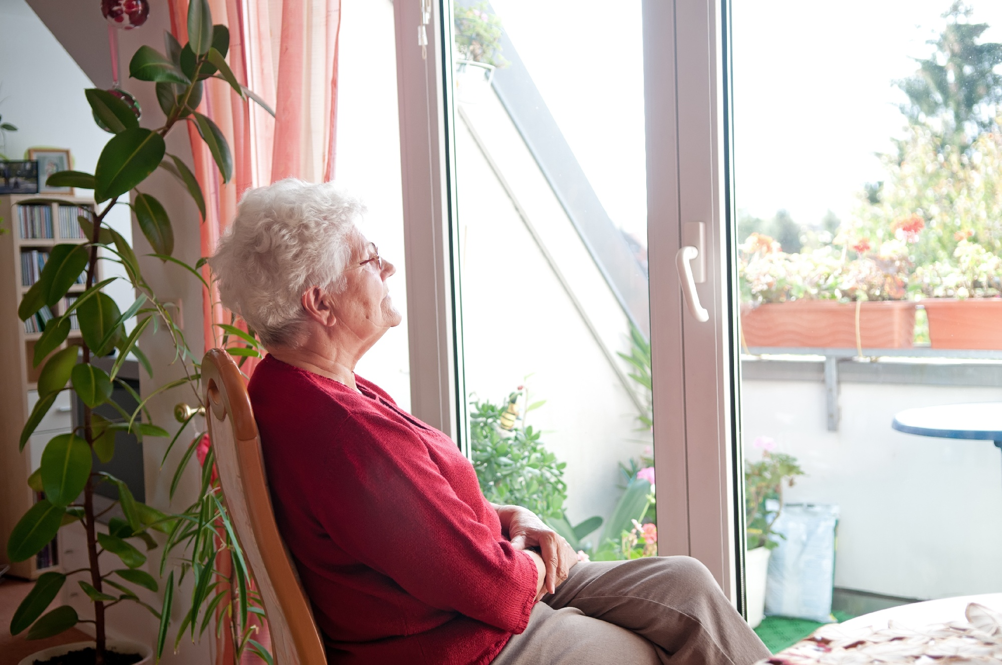 older woman sitting at home looking out